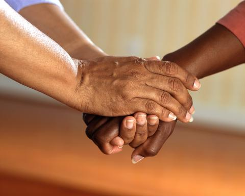 Image of two people joining hands