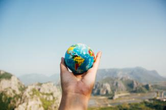 Image of a person holding a globe in their hand